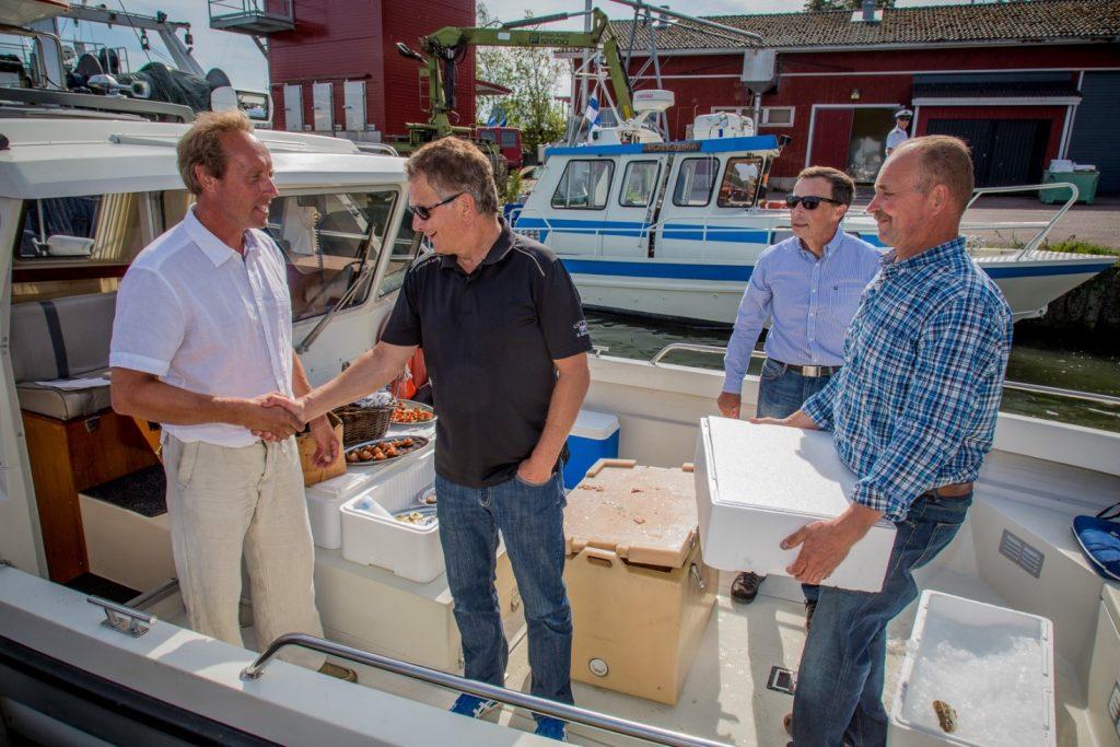 Presidenten tackar båtförare Kalle Olkinuora för färden och dagens fångst följer med till Gullranda. Till höger Kim Jordas och Olavi Sahlstén. Bild: Markku Saiha.