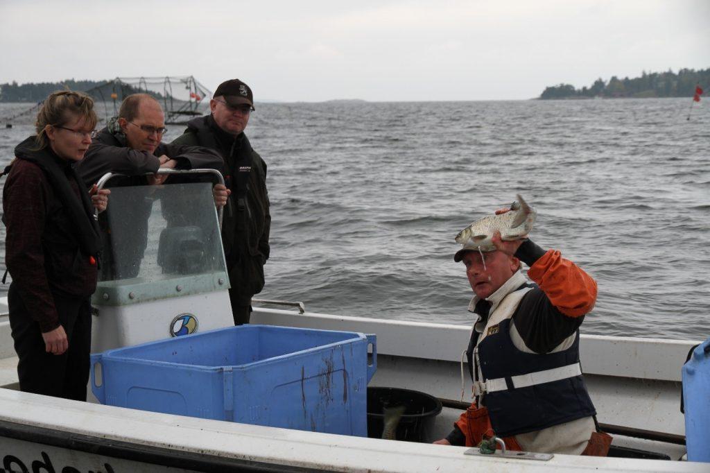 Ledamot Eeva-Maria Maijala, utskottets sekreterare Jaakko Autio och ledamot Jari Lindström med yrkesfiskare Mikael Lindholm. Bild: Kim Jordas.